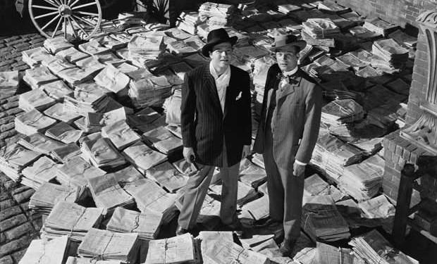 homem pilha de jornais